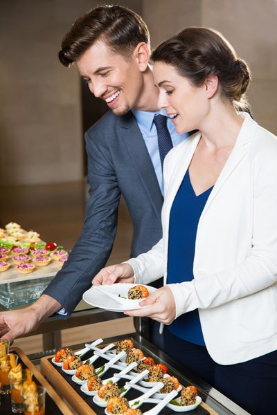 Staff serving themselves at the catering buffet