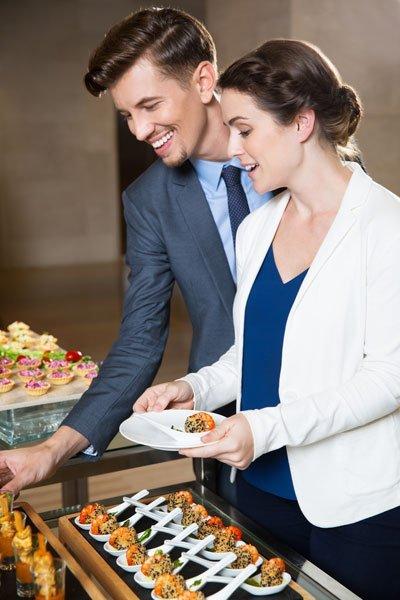 Kollegen bedienen sich an Catering Buffet