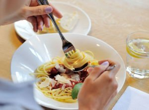 Frau isst Spagetti mit Tomatensauce im Kanne Café Harlaching