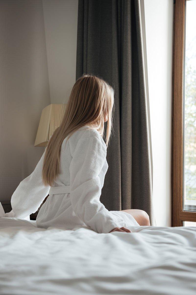 Frau sitzt auf Hotelbett und schaut aus dem Fenster
